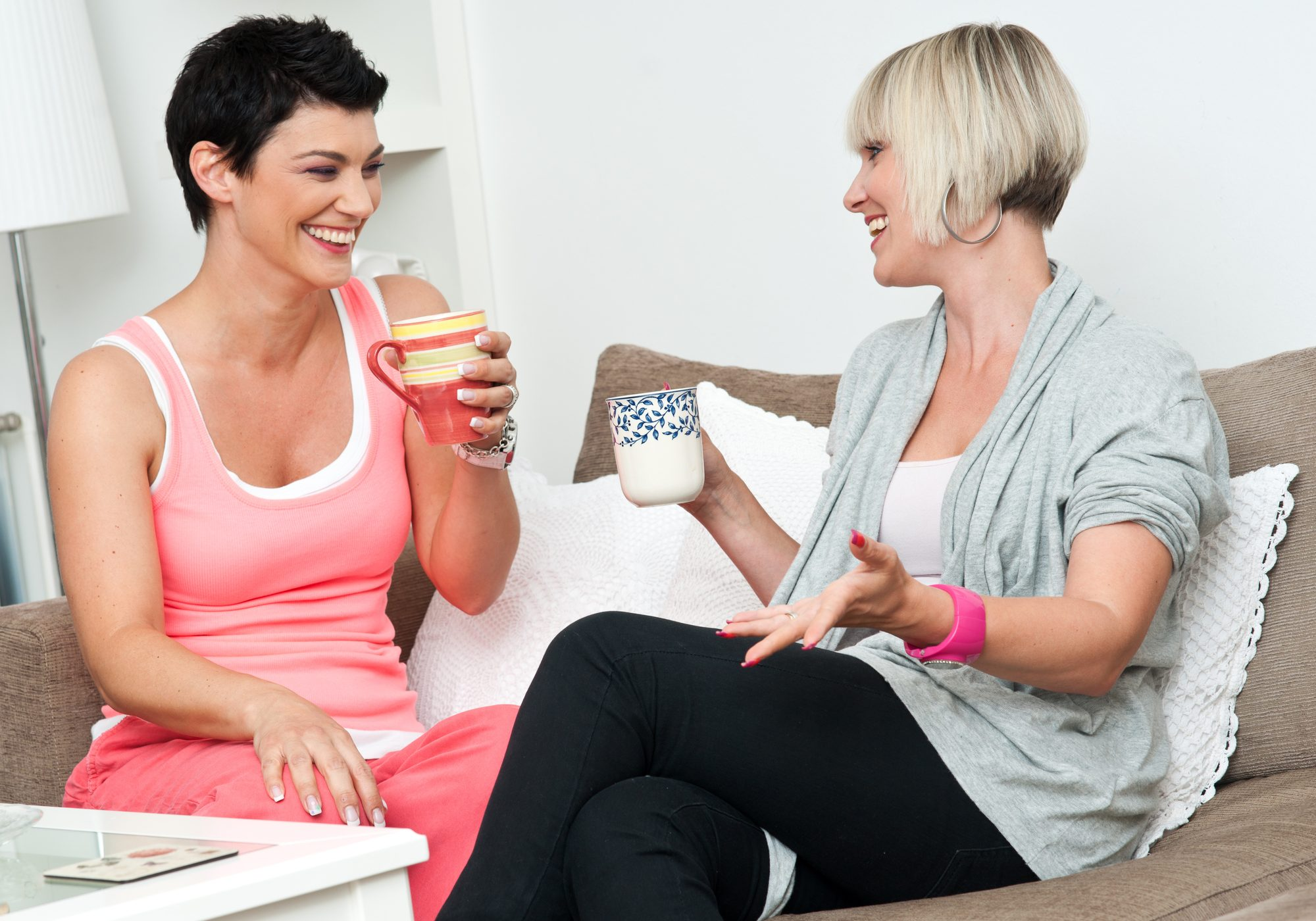 two woman friends chating over coffee and muffins at home